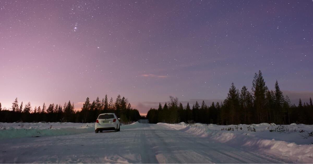 明け方の空の下を走る車
