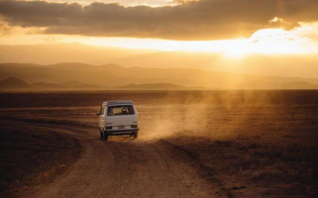 夕暮れを走る車の写真