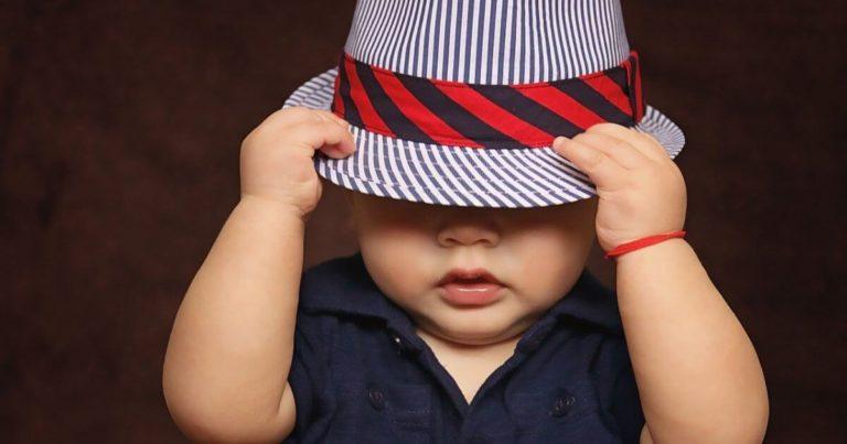 帽子を目深にかぶる赤ちゃんの写真