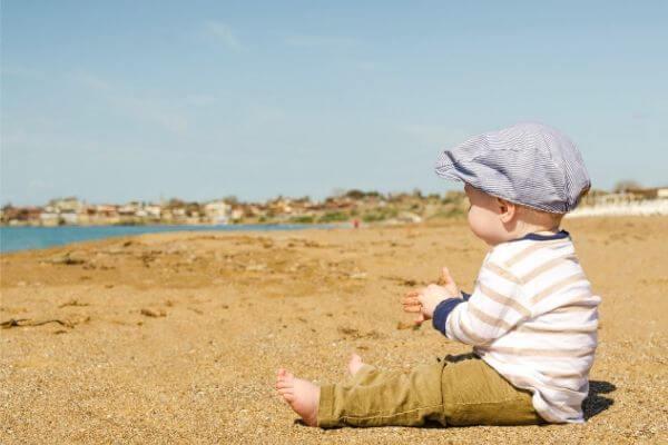 海辺に座る赤ちゃんの写真