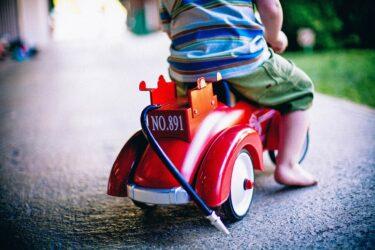 おもちゃの車に乗る子